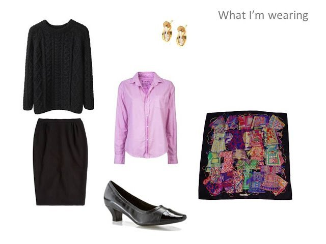 travel outfit of black cabled sweater, pink oxford shirt, black skirt and Hermes scarf
