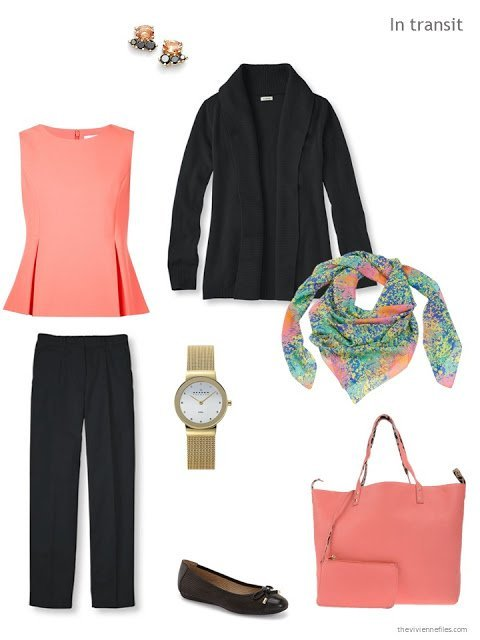 A travel outfit in black and coral, with a coral bag and multi-colored scarf.