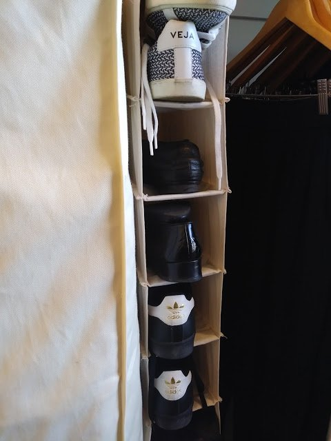 a canvas shoe holder with black and white shoes